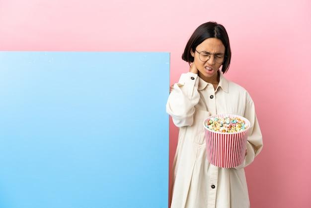 Młoda kobieta rasy mieszanej trzymająca popcorny z dużym banerem na białym tle z bólem szyi