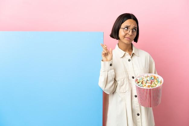Młoda kobieta rasy mieszanej trzymająca popcorny z dużym banerem na białym tle z palcami krzyżującymi się i życzącymi wszystkiego najlepszego