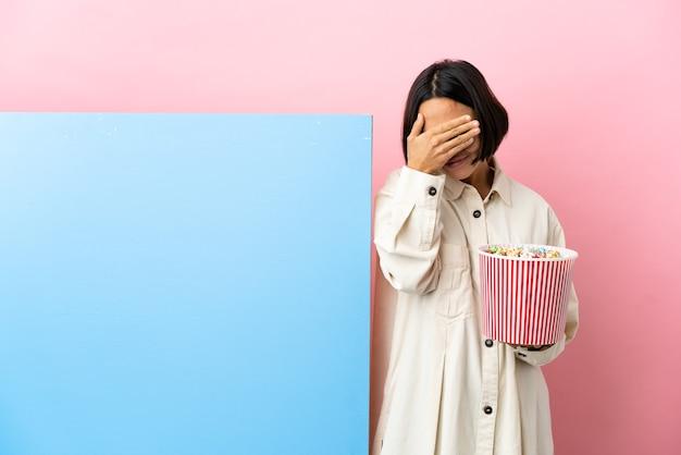 Młoda kobieta rasy mieszanej trzymająca popcorny z dużym banerem na białym tle zakrywającym oczy rękami