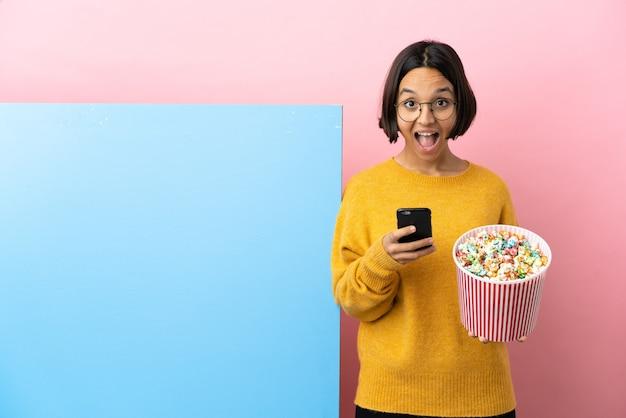 Młoda kobieta rasy mieszanej trzymająca popcorny z dużym banerem na białym tle zaskoczona i wysyłająca wiadomość