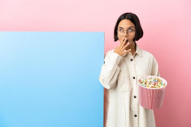Młoda kobieta rasy mieszanej trzymająca popcorny z dużym banerem na białym tle, ziewająca i zakrywająca szeroko otwarte usta dłonią