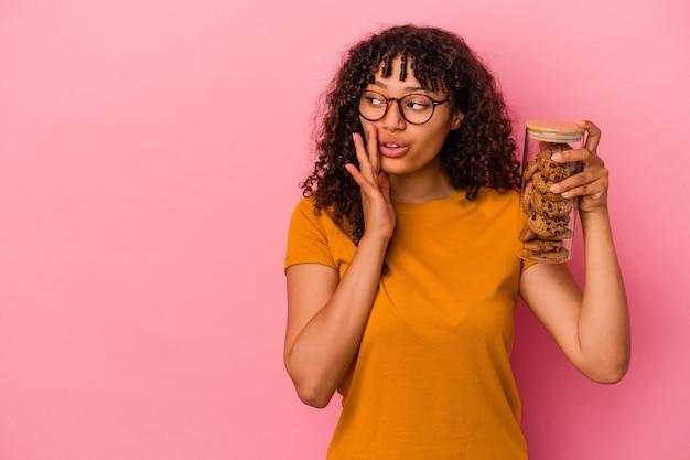 Młoda kobieta rasy mieszanej trzymająca słoik z ciastkami na różowym tle mówi tajne gorące wiadomości o hamowaniu i patrzy na bok