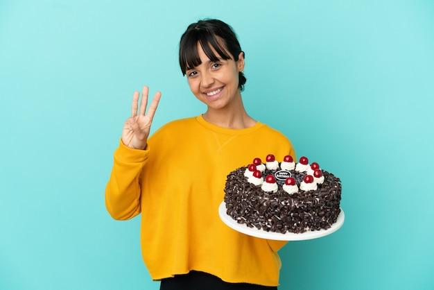 Młoda kobieta rasy mieszanej trzymająca szczęśliwy tort urodzinowy i licząca trzy palcami