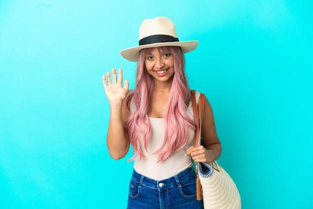 Młoda kobieta rasy mieszanej trzymająca torbę plażową z pamelą odizolowaną na niebieskim tle, pozdrawiając ręką ze szczęśliwym wyrazem twarzy