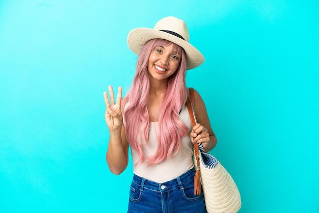 Młoda kobieta rasy mieszanej trzymająca torbę plażową z pamelą odizolowaną na niebieskim tle szczęśliwą i liczącą trzy palcami