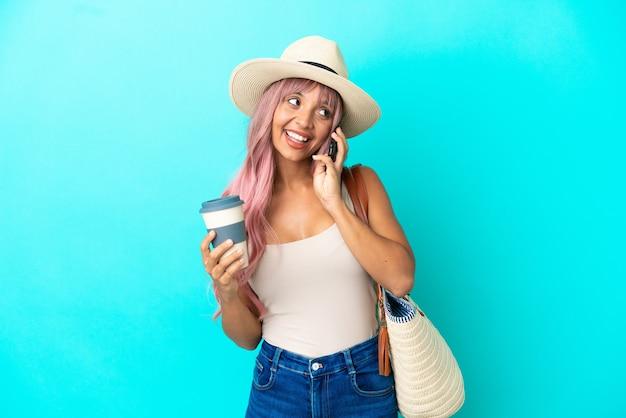 Młoda kobieta rasy mieszanej trzymająca torbę plażową z pamelą odizolowaną na niebieskim tle, trzymającą kawę na wynos i telefon komórkowy