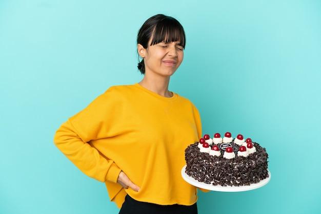 Młoda kobieta rasy mieszanej trzymająca tort urodzinowy cierpiąca na ból pleców za wysiłek