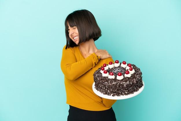 Młoda kobieta rasy mieszanej trzymająca tort urodzinowy cierpiąca na ból w ramieniu za wysiłek