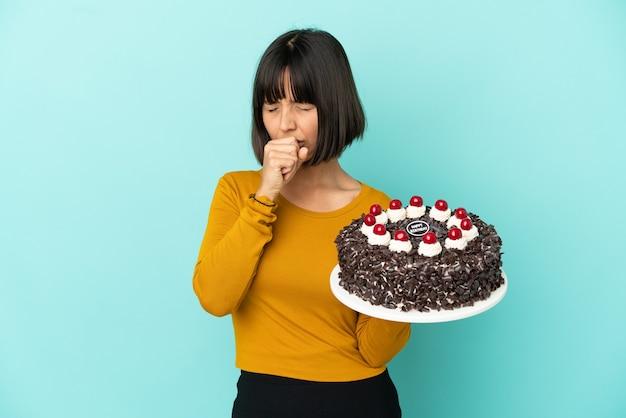 Młoda kobieta rasy mieszanej, trzymająca tort urodzinowy, dużo kaszle
