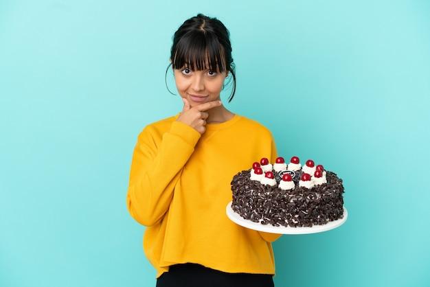 Młoda kobieta rasy mieszanej trzymająca tort urodzinowy i myśląca