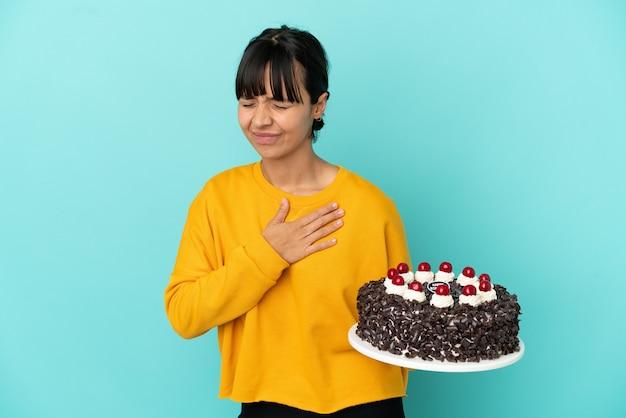 Młoda kobieta rasy mieszanej trzymająca tort urodzinowy mająca ból w sercu