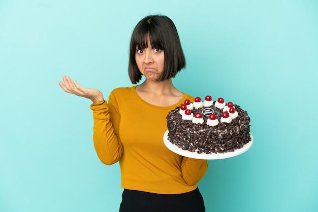Młoda kobieta rasy mieszanej trzymająca tort urodzinowy robiąca gest wątpliwości