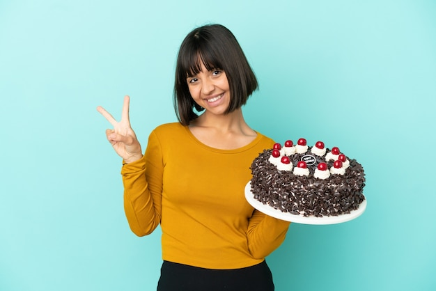Młoda kobieta rasy mieszanej trzymająca tort urodzinowy uśmiechnięta i pokazująca znak zwycięstwa