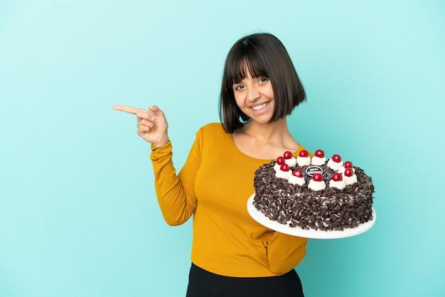 Młoda kobieta rasy mieszanej trzymająca tort urodzinowy wskazujący palec w bok i prezentująca produkt
