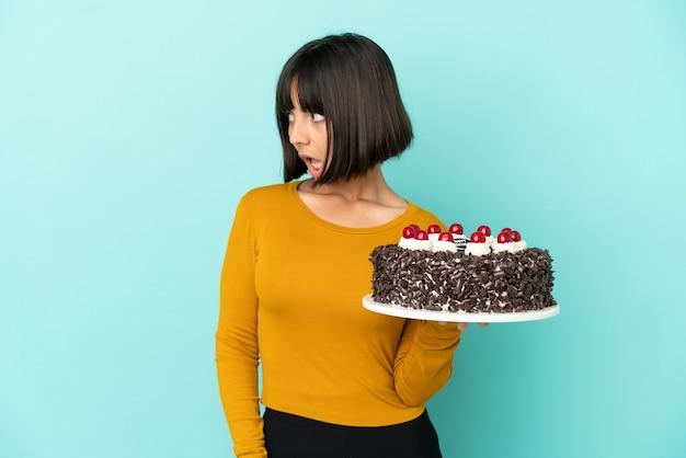 Młoda kobieta rasy mieszanej trzymająca tort urodzinowy wykonująca gest zaskoczenia, patrząc w bok