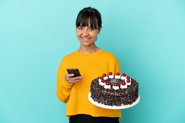 Młoda kobieta rasy mieszanej trzymająca tort urodzinowy wysyłająca wiadomość za pomocą telefonu komórkowego