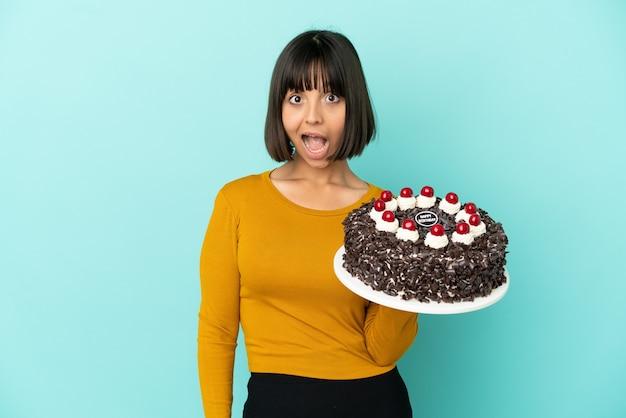Młoda kobieta rasy mieszanej trzymająca tort urodzinowy z niespodzianką na twarzy