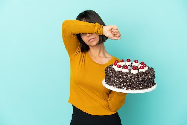 Młoda kobieta rasy mieszanej trzymająca tort urodzinowy zakrywający oczy rękami