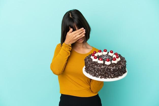 Młoda kobieta rasy mieszanej trzymająca tort urodzinowy ze zmęczoną i chorą miną
