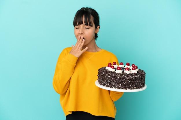 Młoda kobieta rasy mieszanej trzymająca tort urodzinowy ziewający i zakrywający szeroko otwarte usta dłonią