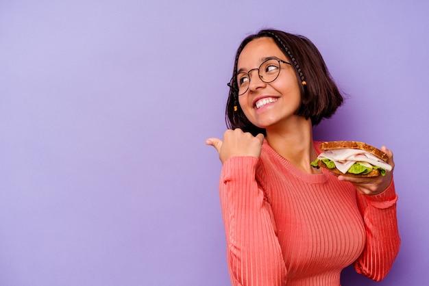 Młoda kobieta rasy mieszanej trzymającej kanapkę na białym tle na fioletowym tle wskazuje palcem kciuka, śmiejąc się i beztrosko.