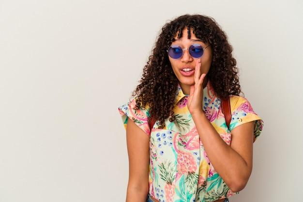 Młoda kobieta rasy mieszanej, ubrana w okulary przeciwsłoneczne, wyjeżdżająca na wakacje na białym tle, mówi sekretną gorącą wiadomość o hamowaniu i spogląda na bok