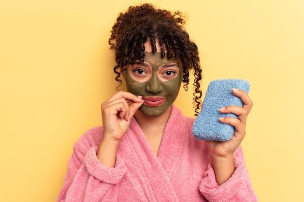 Młoda kobieta rasy mieszanej ubrana w różowy szlafrok trzymając gąbkę pod prysznic na białym tle na żółtym tle z palcami na ustach zachowując tajemnicę.