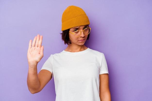 Młoda kobieta rasy mieszanej ubrana w wełnianą czapkę na białym tle na fioletowej ścianie stojącej z wyciągniętą ręką pokazując znak stopu, uniemożliwiając ci.
