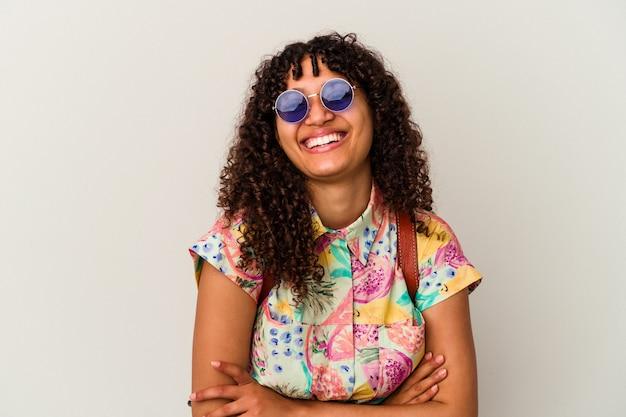 Młoda kobieta rasy mieszanej w okularach na wakacjach na białym tle śmiejąc się i dobrze się bawiąc.
