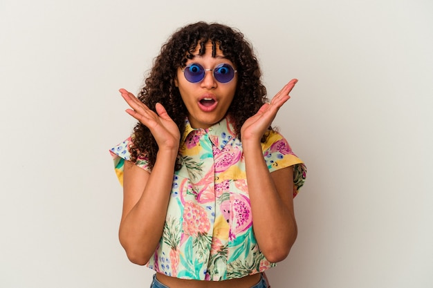 Młoda kobieta rasy mieszanej w okularach na wakacjach na białym tle zaskoczona i zszokowana.