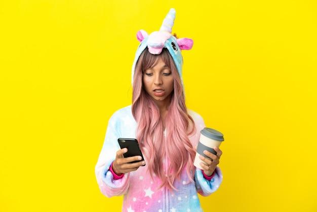Młoda kobieta rasy mieszanej w piżamie jednorożca na białym tle trzymająca kawę na wynos i telefon komórkowy
