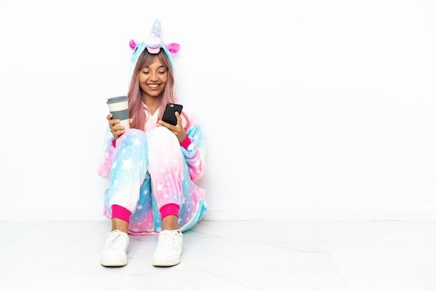 Młoda kobieta rasy mieszanej w piżamie jednorożca, siedząca na podłodze na białym tle, trzymająca kawę na wynos i telefon komórkowy