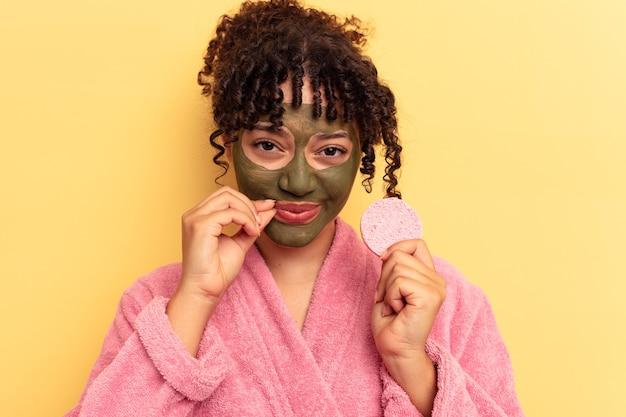 Młoda kobieta rasy mieszanej w szlafroku trzyma gąbkę do demakijażu na białym tle na żółtym tle z palcami na ustach dochowując tajemnicy.