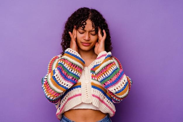 Młoda kobieta rasy mieszanej wyizolowana na fioletowo dotykająca skroni i mająca ból głowy.