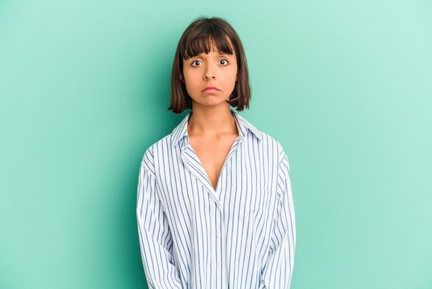 Młoda kobieta rasy mieszanej wyizolowana na niebieską smutną, poważną twarz, czując się nieszczęśliwa i niezadowolona.