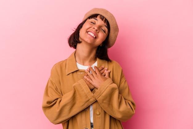 Młoda kobieta rasy mieszanej wyizolowana na różowym tle ma przyjazny wyraz twarzy, przyciskając dłoń do klatki piersiowej. koncepcja miłości.