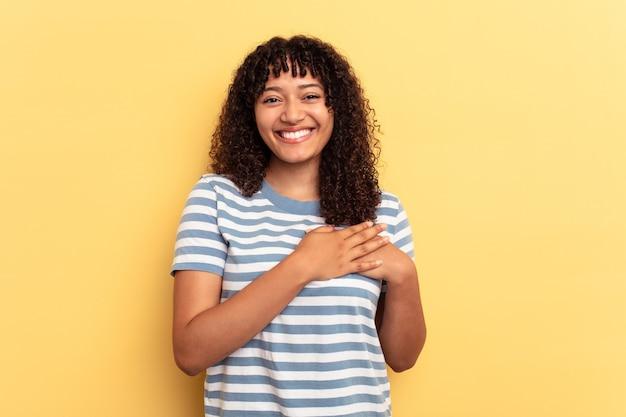 Młoda kobieta rasy mieszanej wyizolowana na żółtym tle ma przyjazny wyraz twarzy, przyciskając dłoń do klatki piersiowej. koncepcja miłości.