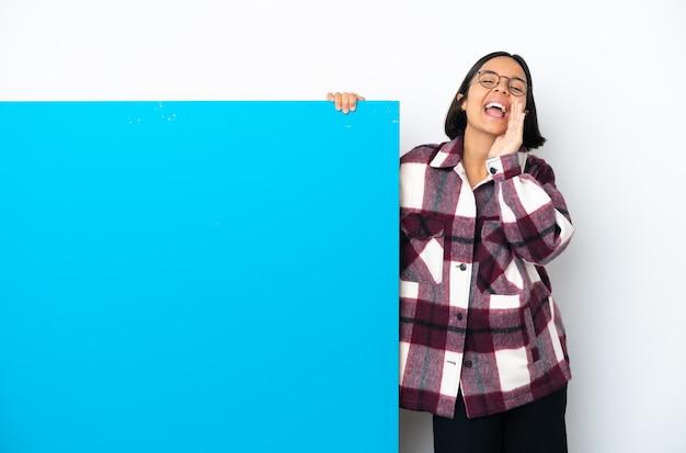 Młoda kobieta rasy mieszanej z dużą niebieską tabliczką na białym tle krzyczącą i ogłaszającą coś