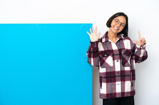 Młoda kobieta rasy mieszanej z dużą niebieską tabliczką na białym tle, licząc siedem palcami