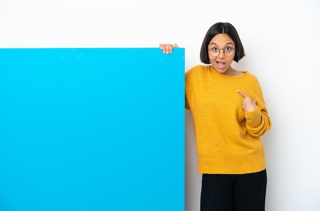 Młoda kobieta rasy mieszanej z dużą niebieską tabliczką na białym tle z niespodzianką wyrazem twarzy