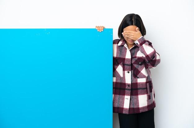 Młoda kobieta rasy mieszanej z dużą niebieską tabliczką na białym tle zakrywającą oczy rękami