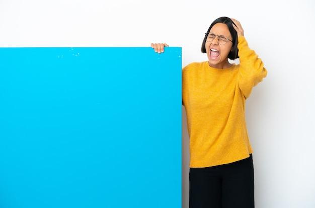 Młoda kobieta rasy mieszanej z dużą niebieską tabliczką na białym tle, zestresowana, przytłoczona