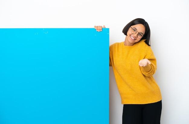 Młoda kobieta rasy mieszanej z dużym niebieskim plakietką na białym tle trzymając copyspace wyimaginowane na dłoni, aby wstawić reklamę