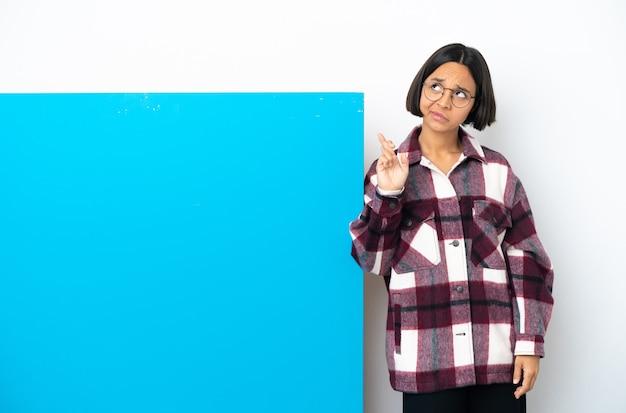 Młoda kobieta rasy mieszanej z dużym niebieskim plakietką na białym tle z palcami skrzyżowanymi i życząc wszystkiego najlepszego