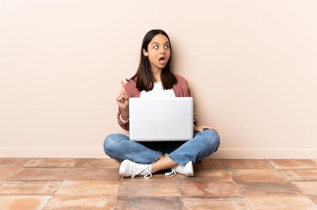Młoda kobieta rasy mieszanej z laptopem siedząc na podłodze, myśląc pomysł, wskazując palcem w górę