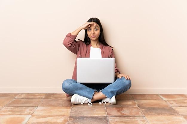 Młoda kobieta rasy mieszanej z laptopem siedząc na podłodze pozdrawiając