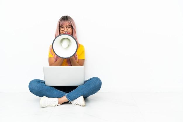 Młoda kobieta rasy mieszanej z laptopem z różowymi włosami siedząca na podłodze na białym tle krzycząca przez megafon