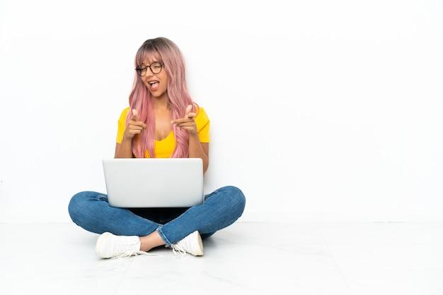Młoda kobieta rasy mieszanej z laptopem z różowymi włosami siedząca na podłodze na białym tle, skierowana do przodu i uśmiechnięta