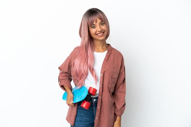 Młoda kobieta rasy mieszanej z różowymi włosami na białym tle z łyżwą