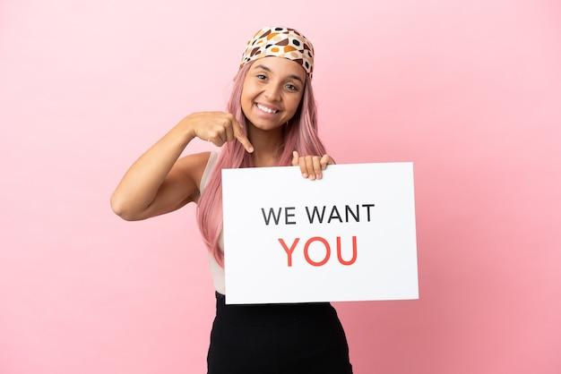 Młoda kobieta rasy mieszanej z różowymi włosami na różowym tle trzymająca tablicę we want you i wskazującą ją